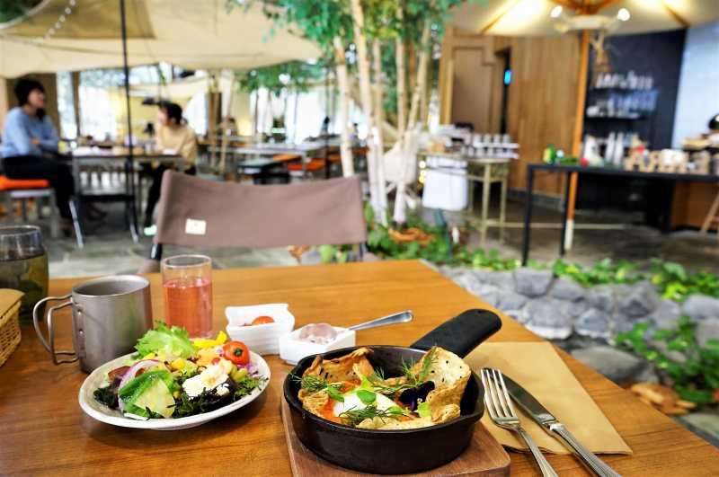 アウトドアのような雰囲気の緑あふれる店内にあるテーブルに、食事が置いてある様子