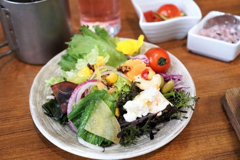 色とりどり野菜サラダやドリンクがテーブルに置かれている