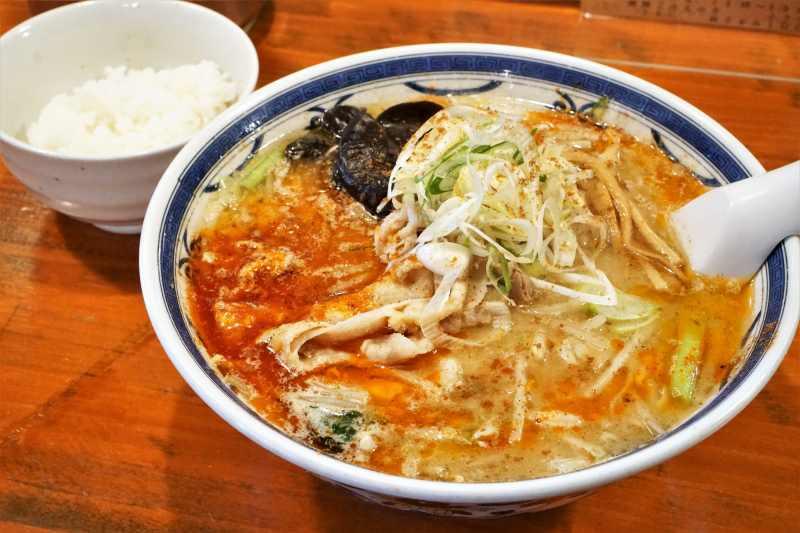 スープがラー油で覆われた「薬膳香辛(シャンカラ)味噌 中辛」とライスがテーブルに置かれている