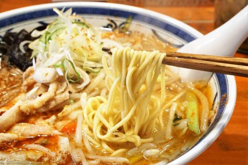 「薬膳香辛(シャンカラ)味噌 中辛」の麺を箸で持ち上げている様子