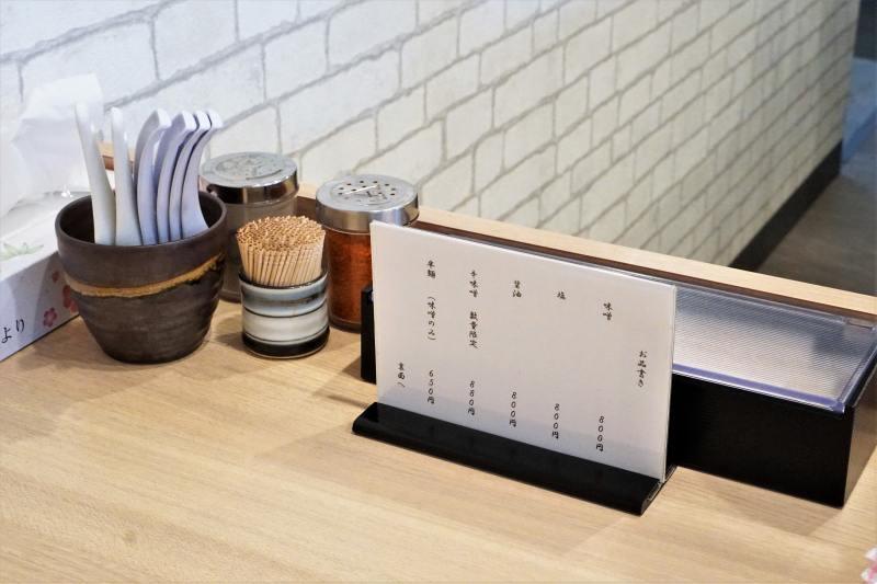 レンゲや一味などが置かれている、「札幌麺屋 美椿」のテーブル上の様子