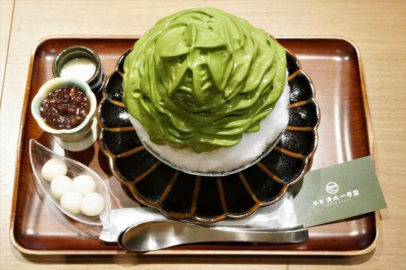 「茶匠 清水一芳園 三井アウトレットパーク札幌北広島店」の「特製宇治抹茶エスプーマかき氷」とトッピングがテーブルに置かれている