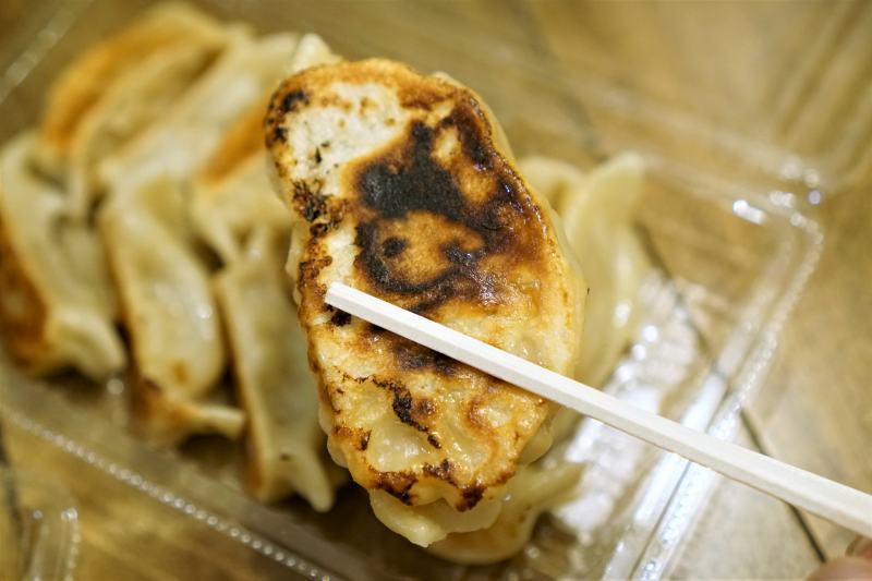 猿のジャンボ餃子を箸で持ちあげている様子