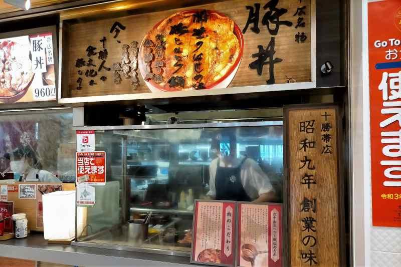 豚丼のぶたはげ北広島店の店頭で、スタッフが豚肉を焼いている様子