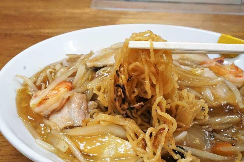 あんかけ焼きそばの中華麺を箸で持ち上げている様子