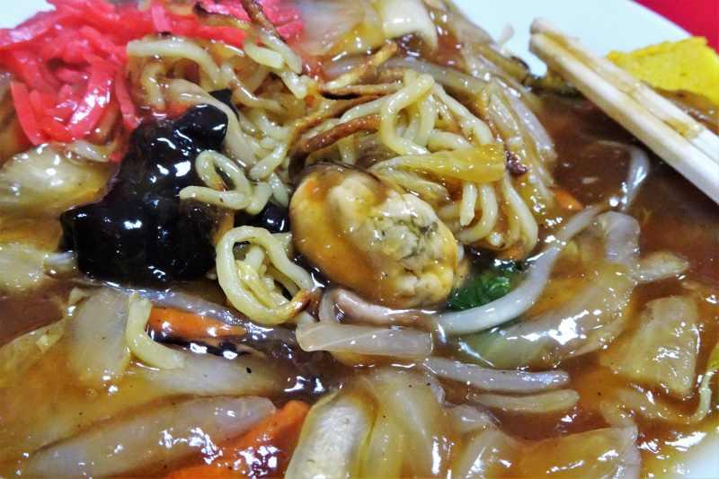 ムール貝がはいっているあんかけ焼きそばがお皿に盛られている