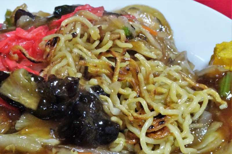 麺に焼き目がついたあんかけ焼きそばがお皿に盛られている