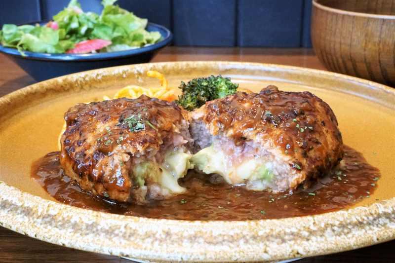 アボカドとチーズが入ったハンバーグとサラダがテーブルに置かれている