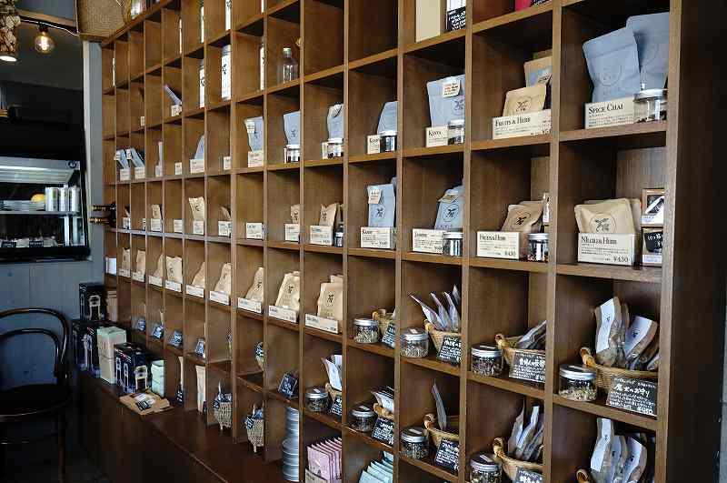 木の棚に紅茶やハーブティーが並べられている