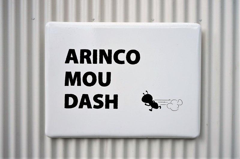 モノクロカラーの「アリンコモウダッシュ」店名看板が外壁に貼られている
