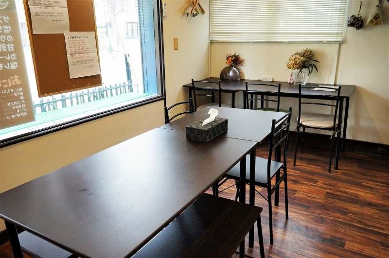 黒いテーブルと椅子が並ぶザンギ専門店 朧の内観