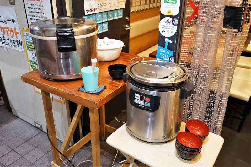 炊飯器、大きなお鍋などがテーブルに置かれている