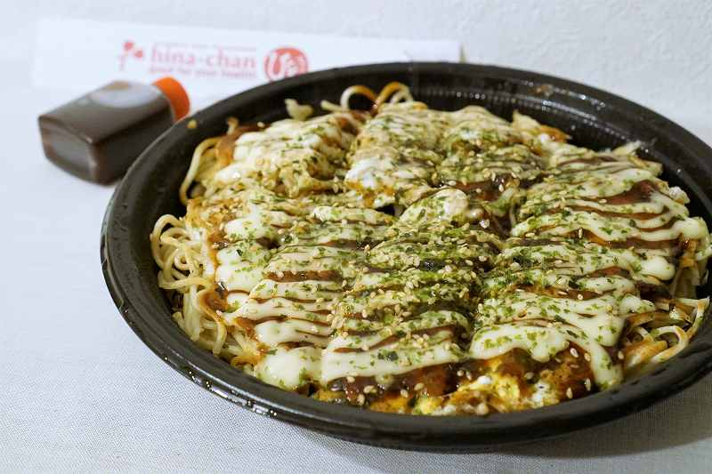 広島お好み焼き ひなちゃんの「タコ肉玉そば」とソースがテーブルに置かれている