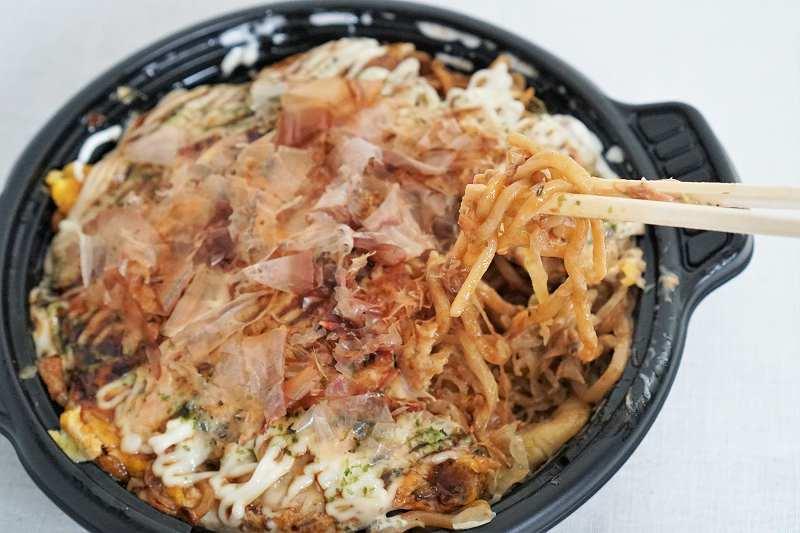 お好み焼きと鉄板めしの あちちの「MIXモダン焼き」の麺を箸で持ち上げている様子