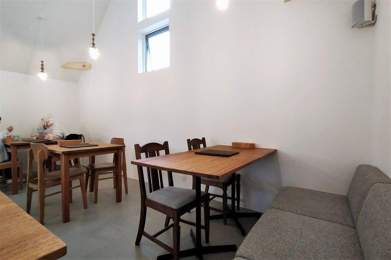 木のテーブルとイスが置かれている「アリンコモウダッシュ」の店内