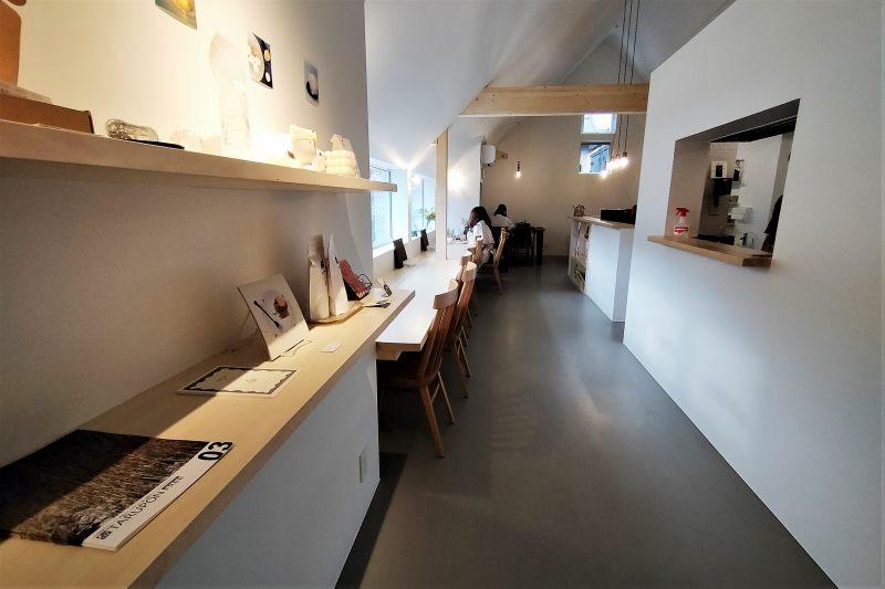 白木のカウンターテーブルと木のイスが置かれている「アリンコモウダッシュ」の内観
