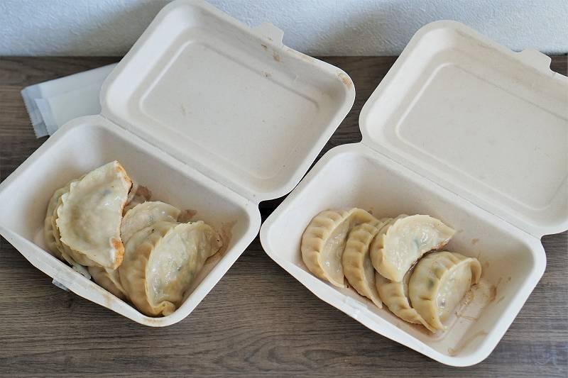 紙箱に入った焼き餃子がテーブルに置かれている