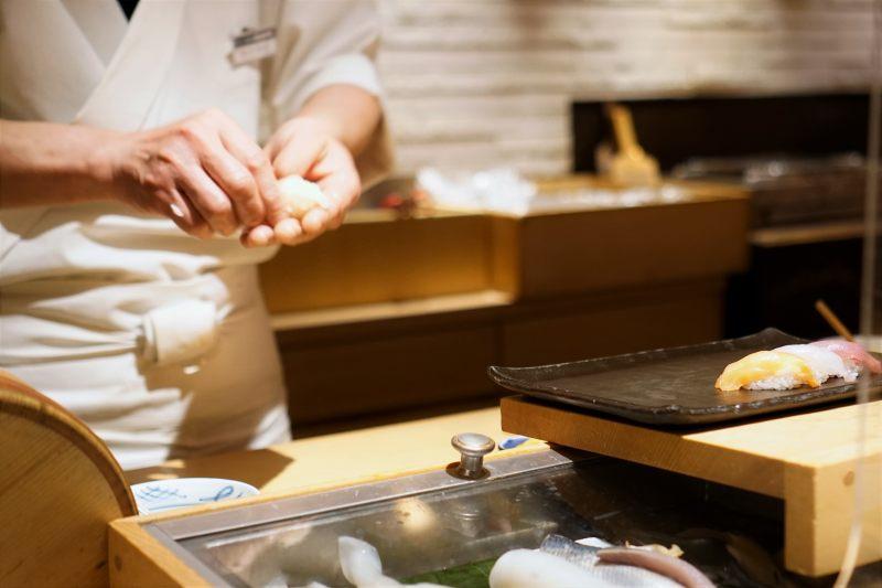 カウンター越しに寿司職人が寿司を握っている様子