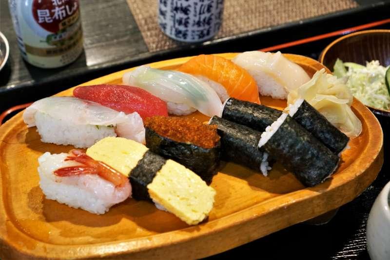 お寿司と巻物がテーブルに置かれている