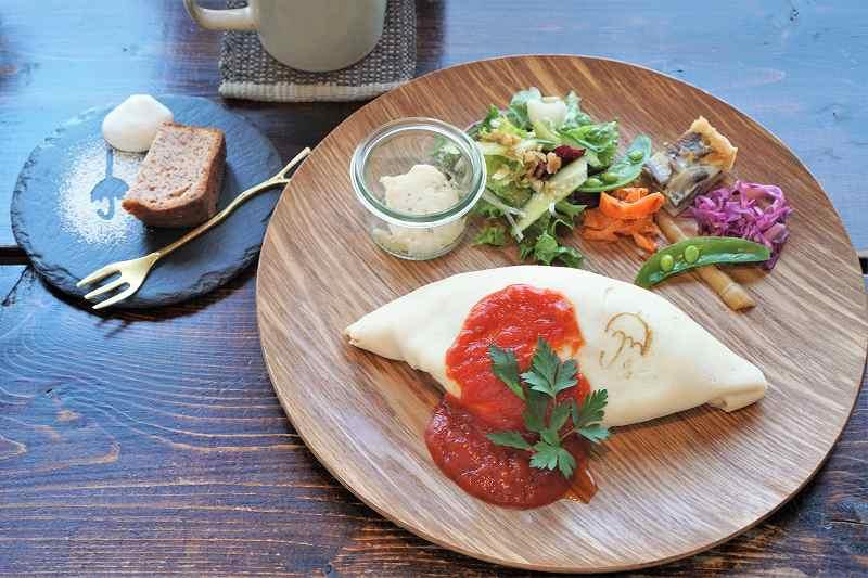 白いオムライスプレートとパウンドケーキ、ドリンクがテーブルに置かれている
