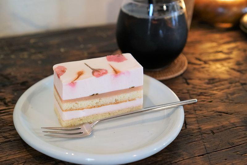 桜のケーキとアイスコーヒーがテーブルに置かれている
