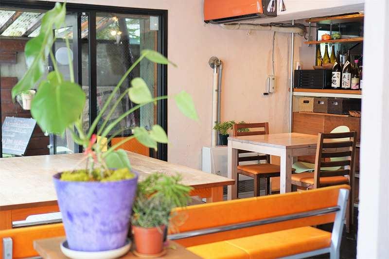 木のテーブルとオレンジのイスが置かれた「青い空流れる雲」の店内