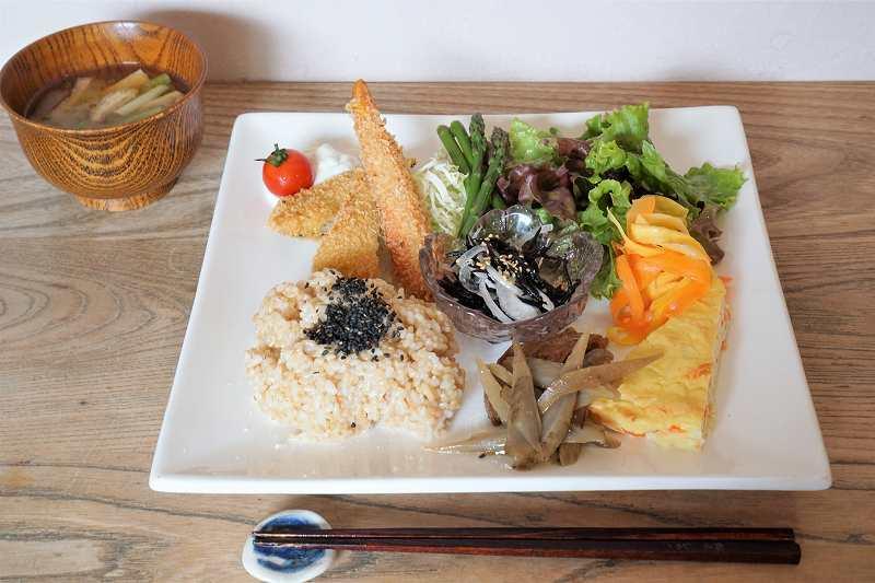 玄米ごはんや野菜のおかずのプレートと味噌汁がテーブルに置かれている