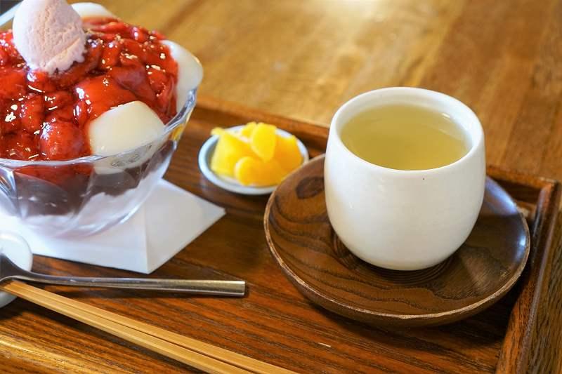 苺ぜんざい白玉入りと日本茶、お漬物がテーブルに置かれている