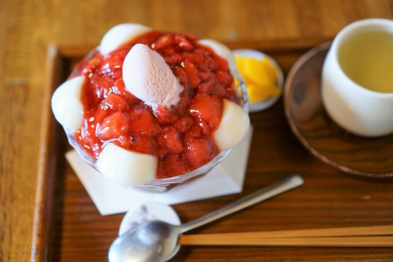 白玉入りの苺ぜんざいとお茶がテーブルに置かれている