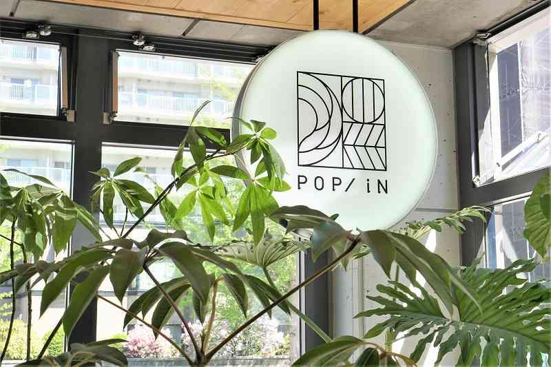 モノトーンのシンプルな「POP/iN(ポップイン)」の看板が天井からつるされている