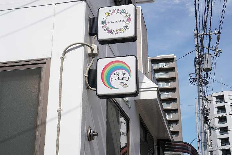 「pudding maruyama(プディングマルヤマ)」の白い店名看板