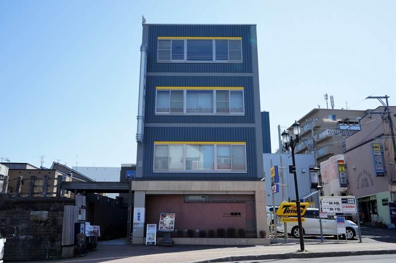 寿司屋通り沿いに建つ、ブルーの外壁のおたる政寿司本店外観