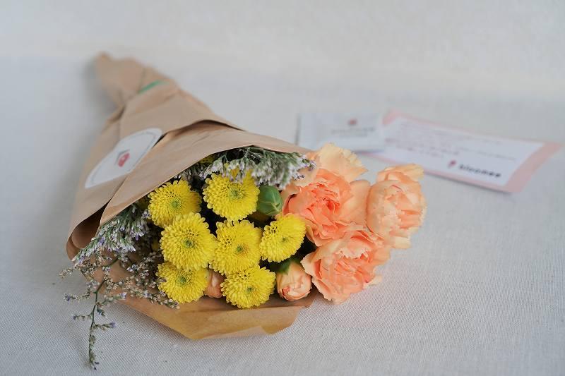 オレンジ、イエローなどのお花のブーケがテーブルに置かれている