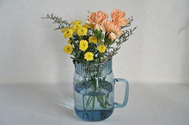 オレンジや黄色のお花が花瓶に入ってテーブルに置かれている