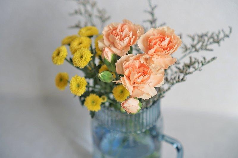 お花がブルーの花瓶に入れられている様子