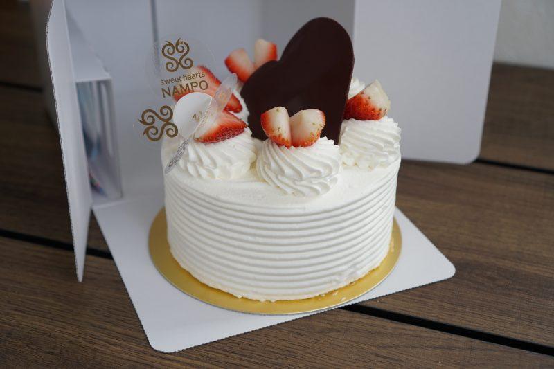 スイートハーツナンポの生クリームデコレーションケーキがテーブルに置かれている