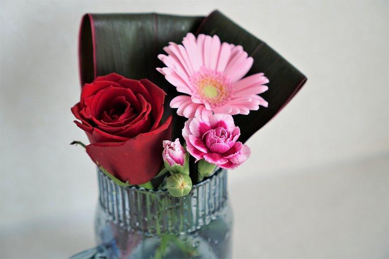 バラやガーベラなどが花瓶に入れられ、テーブルに置かれている