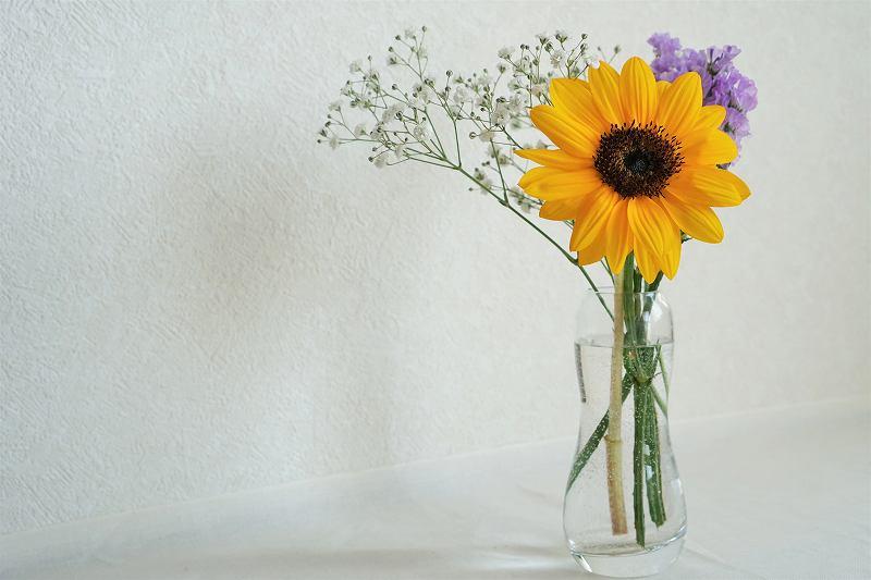 ひまわりのミニブーケが花瓶に入れられ、テーブルに置かれている