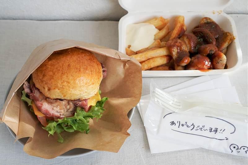 アイスバインがサンドされたグルメバーガーと、ポテトとソーセージがテーブルに置かれている