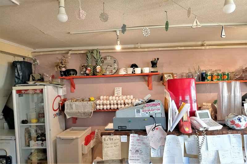 壁の棚にたまごが並ぶ「八百屋 かしま商店」の内観