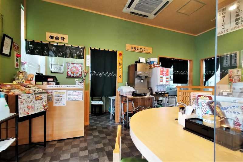 淡いグリーンの壁の「回転寿司うずしお 高島店」の内観