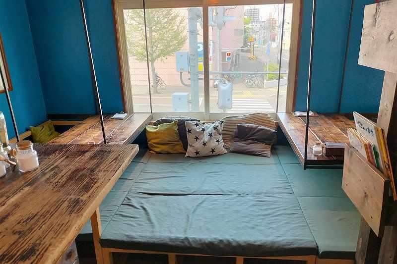 カフェレインの店内にある、クッションが置かれた木のテーブルの小上がり席