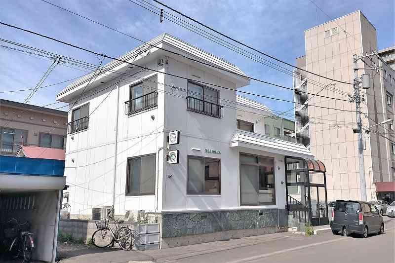 白い外壁の「pudding maruyama(プディングマルヤマ)」の外観