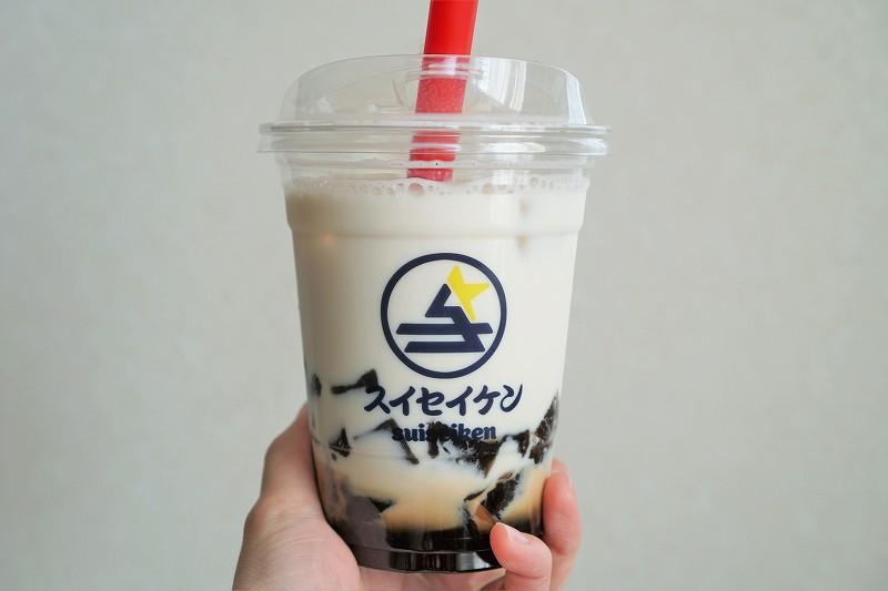 NEO和菓子 彗星軒のトロモチドリンク「黒蜜ミルク × 黒糖わらび餅」を手に持っている様子