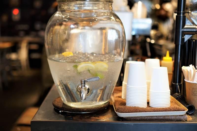 レモン、ミントが入ったウォーターサーバーと紙コップが台に置かれている