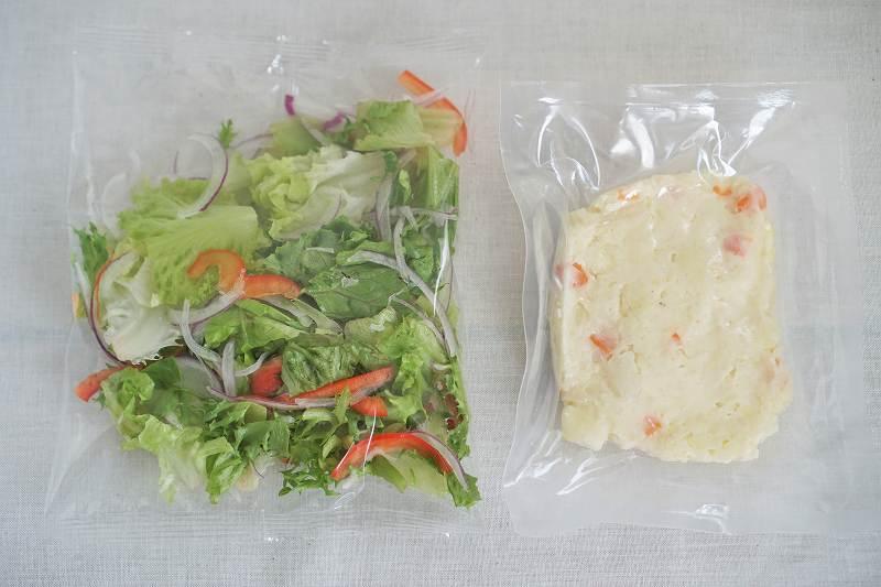 袋に入った生野菜とポテトサラダがテーブルに置かれている