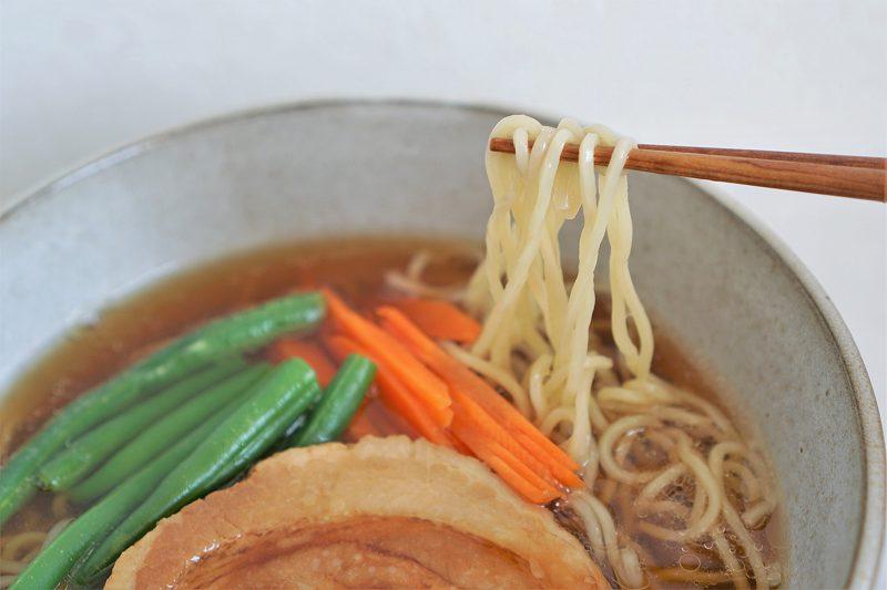 ラーメンの麺を箸で持ちあげている様子