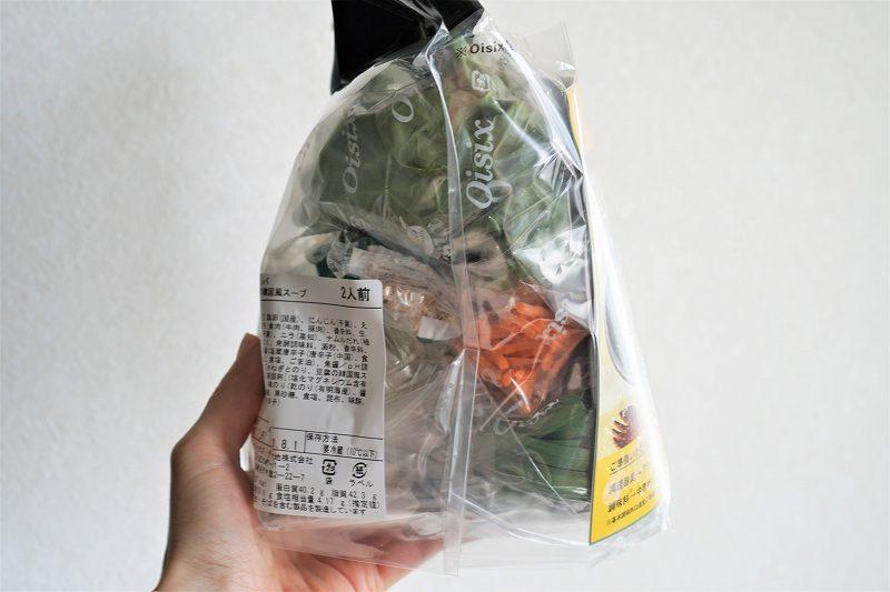 Kit Oisix(キットオイシックス)そぼろと野菜のビビンバとスープのセットを手に持っている様子