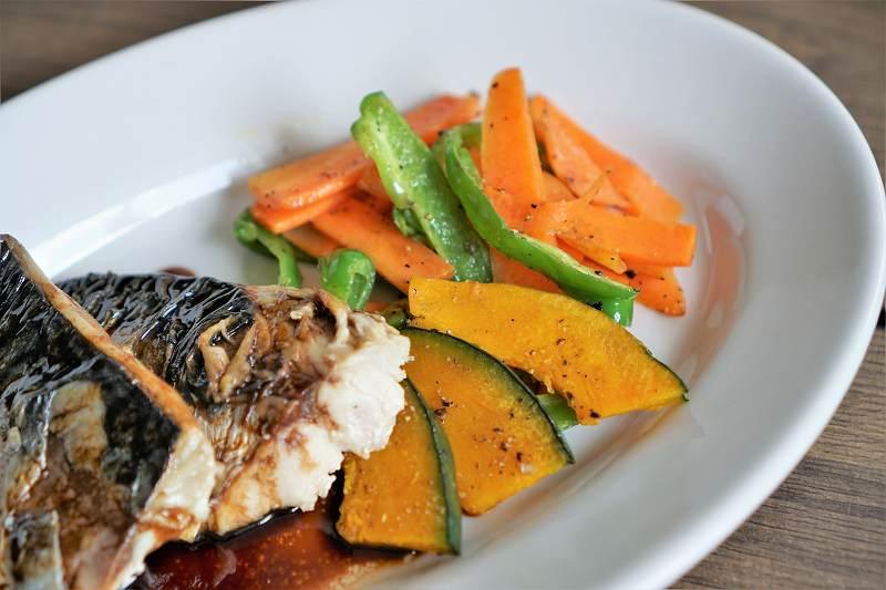 焼き野菜がサバと一緒に皿に盛られている