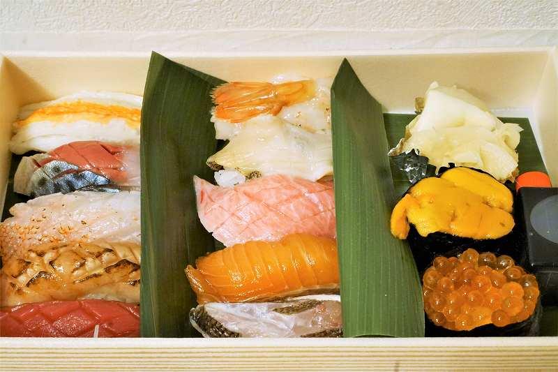 カニやとろなどのお寿司の折がテーブルに置かれている